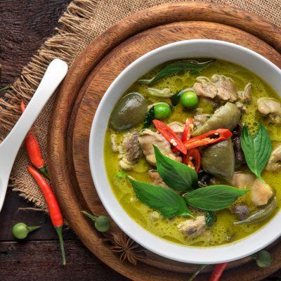 Grünes Thai Curry mit Huhn auf dunklen hölzernen Hintergrund. Ansicht von oben